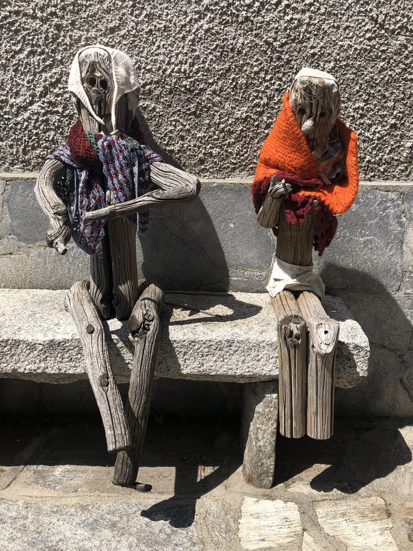 Two old ladies basking in the sun with their shawls in Musignano