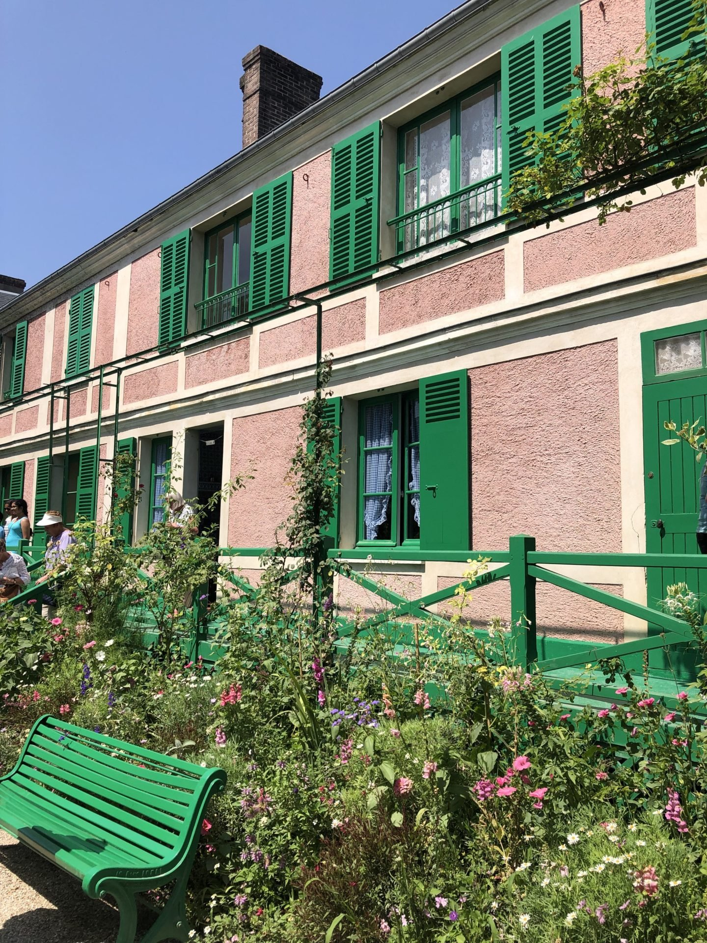 The Monet house in Giverny front veranda painted in pink and green