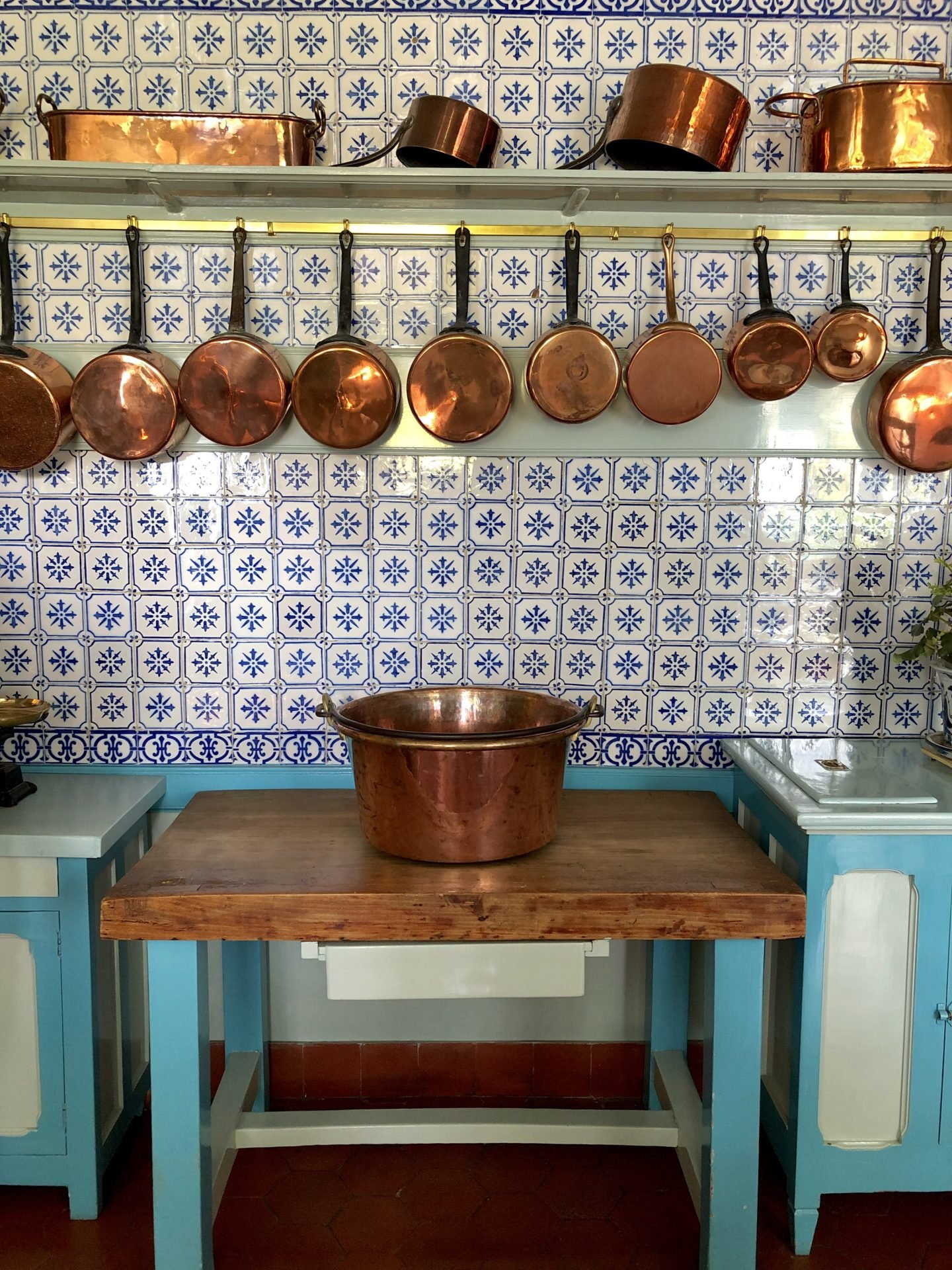 The tiles on Claude Monets kitchen walls are from Rouen and the copper pots contrast  with the blue and white tiles.