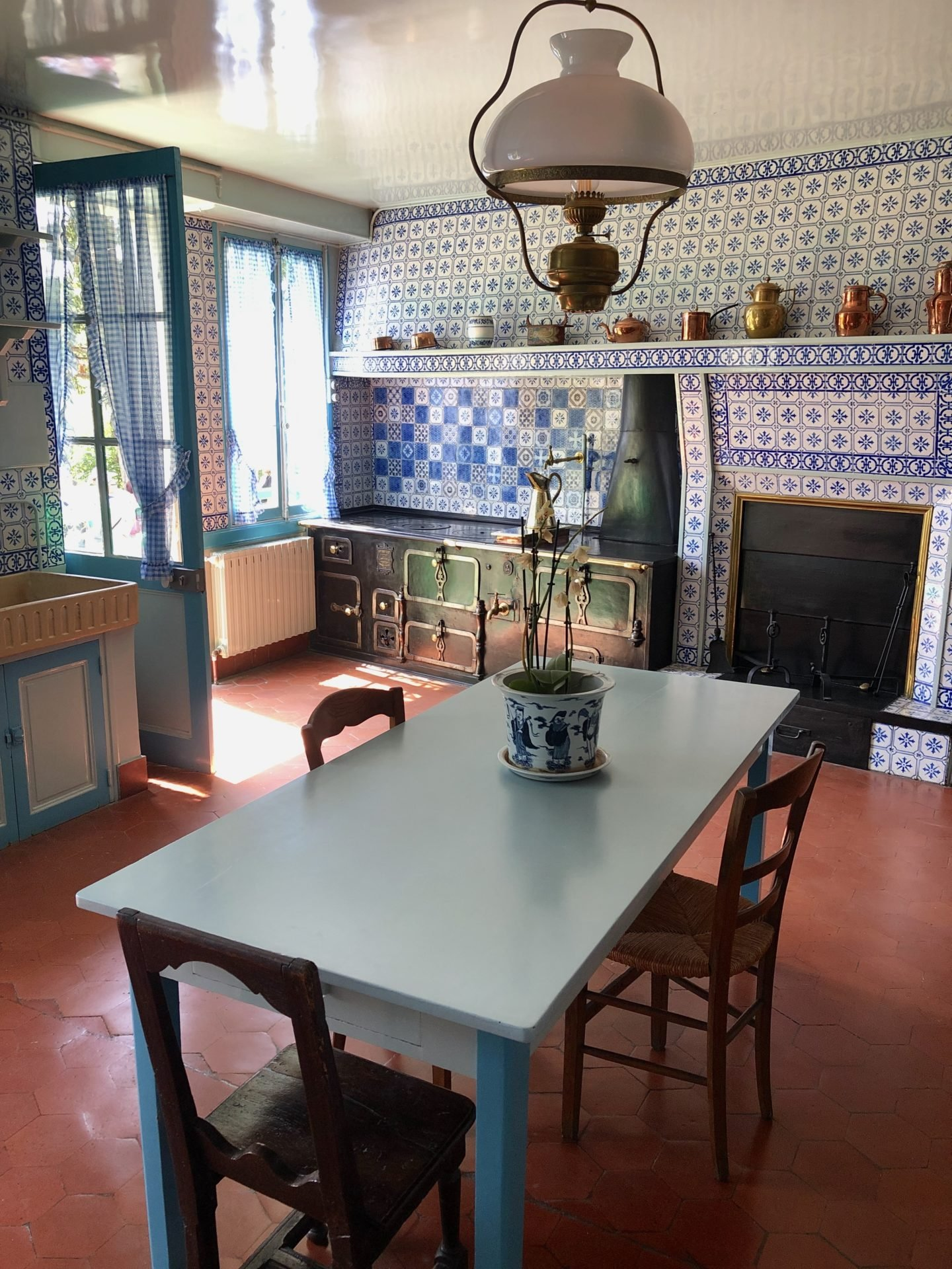 The Blue kitchen in the Monet House with tiles from Rouen. A huge oven sits in the corner.